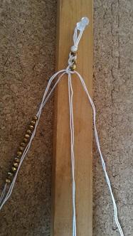 木の棒にピンを刺し、糸を押さえるようにして編み込んでいってます